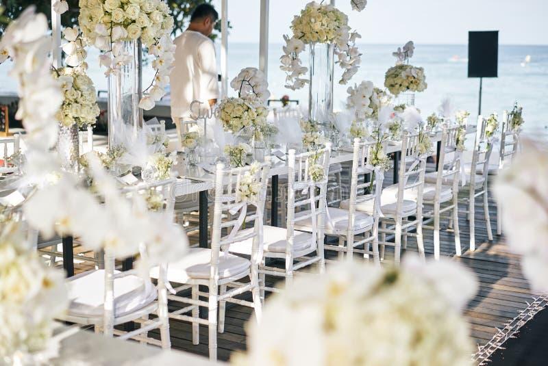 Der Hochzeitsort für den AufnahmeAbendtisch verziert mit weißen Orchideen, weiße Rosen, Blumen, Blumen-, weiße chiavari Stühle stockbilder