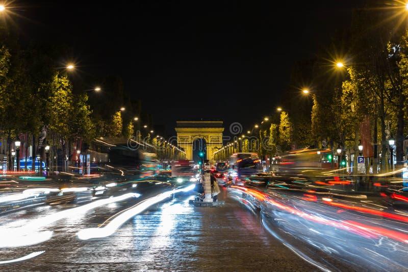 Der hohe Verkehr (unscharfe Bewegung) auf Allee Champs-Elysees am nig stockbild