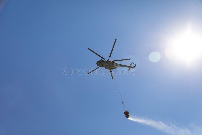 Der Hubschrauber setzt heraus das Feuer und gießt Wasser von einer hängenden Kapazität des APU stockfotos