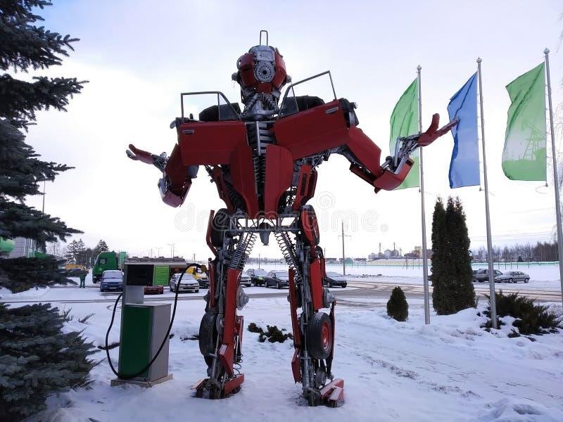 Der humanoid Metalllustige Roboter das rote autoboat, wird von den Ersatzteilen des Autos, wieder tankt Benzin, Teile des Körpers stockbilder