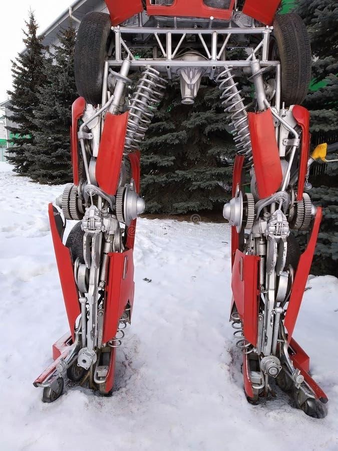 Der humanoid Metalllustige Roboter das rote autoboat, wird von den Ersatzteilen des Autos, wieder tankt Benzin, Teile des Körpers stockfotos