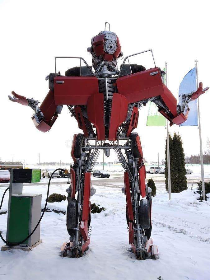 Der humanoid Metalllustige Roboter das rote autoboat, wird von den Ersatzteilen des Autos, wieder tankt Benzin, Teile des Körpers lizenzfreies stockfoto