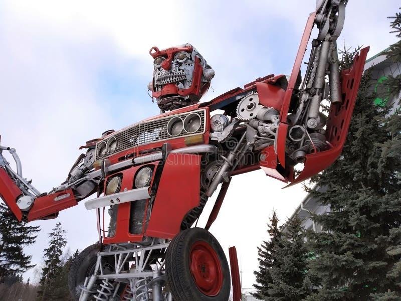 Der humanoid Metalllustige Roboter das rote autoboat, wird von den Ersatzteilen des Autos, wieder tankt Benzin, Teile des Körpers lizenzfreie stockfotografie