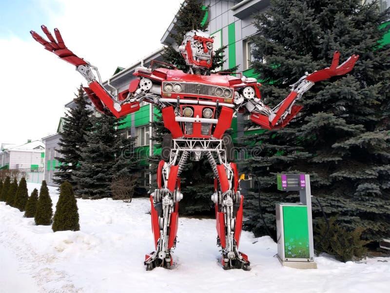 Der humanoid Metalllustige Roboter das rote autoboat, wird von den Ersatzteilen des Autos, wieder tankt Benzin, Teile des Körpers lizenzfreies stockbild