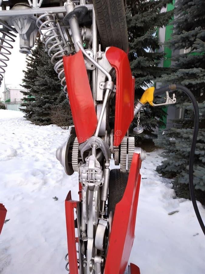 Der humanoid Metalllustige Roboter das rote autoboat, wird von den Ersatzteilen des Autos, wieder tankt Benzin, Teile des Körpers stockfoto