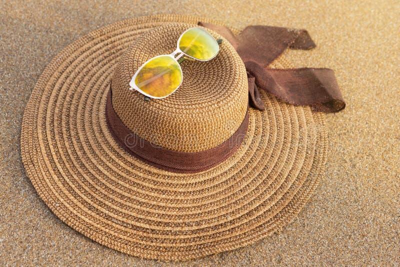 Der Hut und die Sonnenbrille Brown-Frauen auf nass Sand an der Küste, Konzept des Sommers lizenzfreies stockfoto