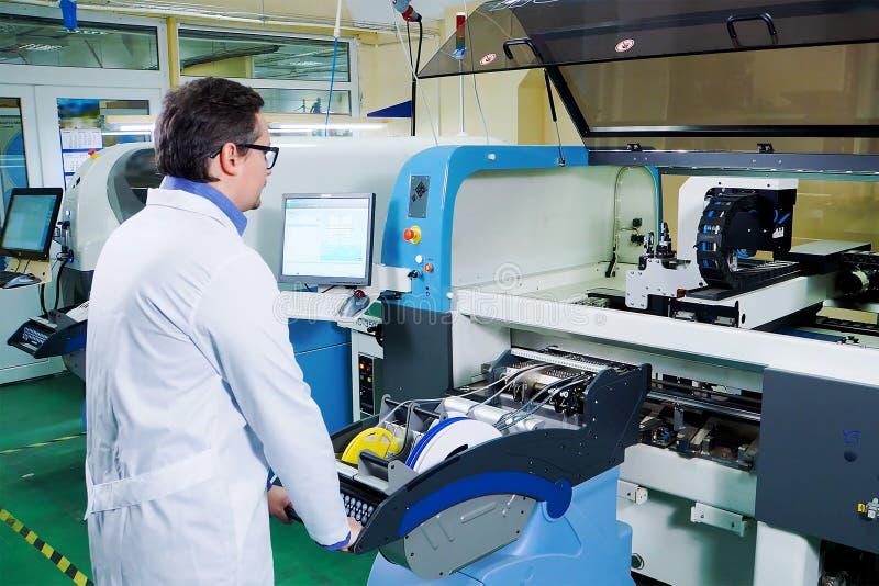 Der Ingenieur in einer weißen Robe und Glasarbeiten für die Oberflächenberg-Technologiemaschine PWB, das auf CNC-Maschine verarbe lizenzfreie stockfotografie