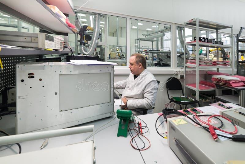 Der Ingenieur führt einen Test der fertigen elektronischen Module durch Labor für die Prüfung und Anpassung von elektronischem lizenzfreie stockfotografie