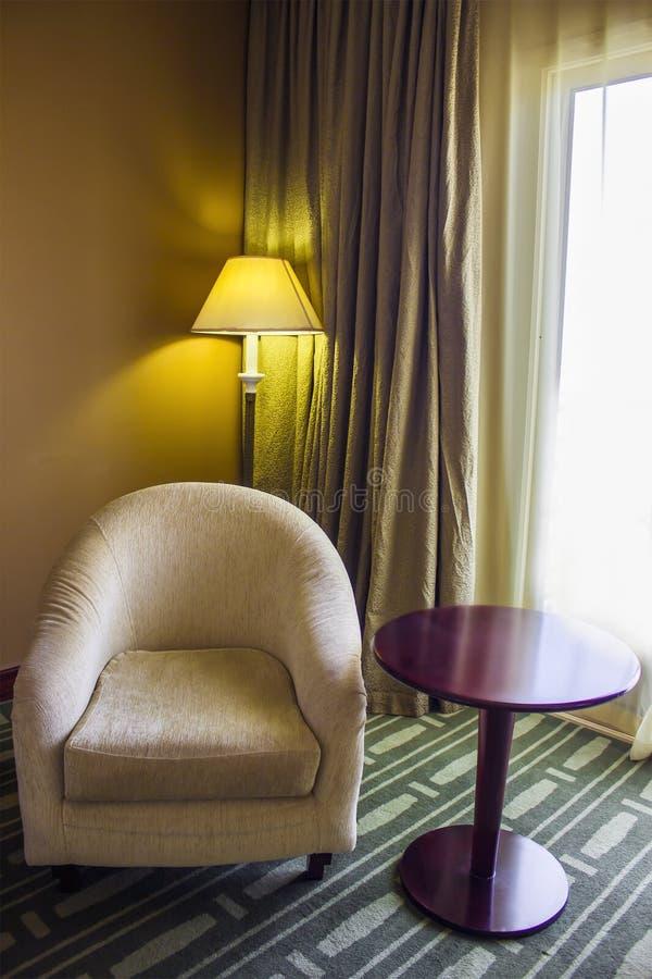 Der Innenraum des Raumes ist ein Lehnsessel, ein Rundtisch, der vom Mahagonibaum gemacht werden und eine Stehlampe im Hintergrund lizenzfreie stockfotos