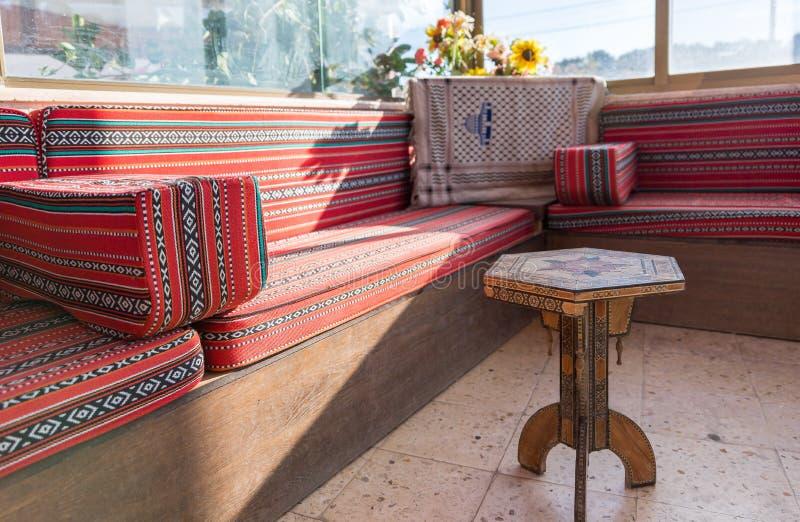 Der Innenraum des Straßenrandrestaurants nahe der Stadt Madaba in Jordanien Dekorative Tabelle und Sofas in der Ecke des Gastraum lizenzfreies stockfoto