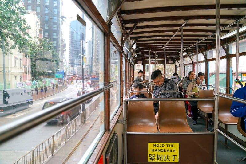Der Innenraum einer Tram in Hong Kong mit Pendlern und der Ansicht des älteren Stadtteiles lizenzfreie stockbilder
