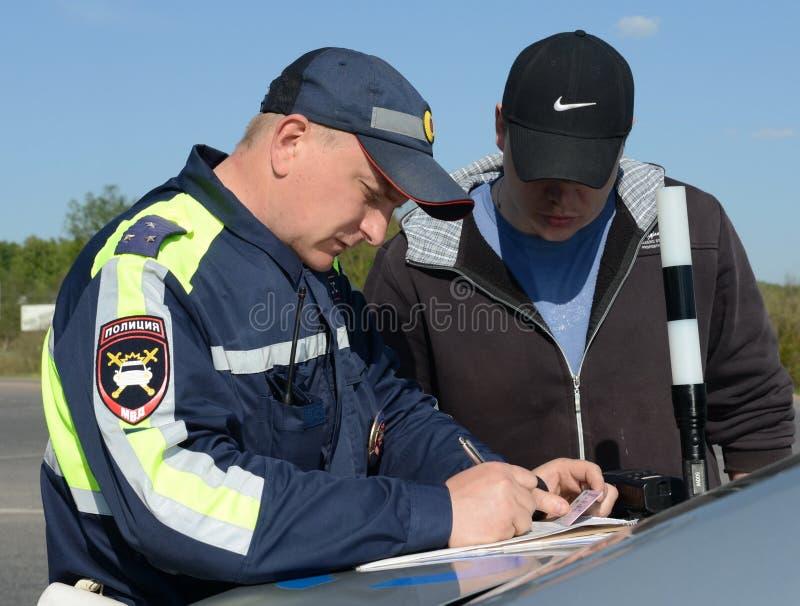 Der Inspektor der Verkehrspolizei stellt ein Protokoll auf Verletzung von Verkehrsregeln auf lizenzfreies stockbild