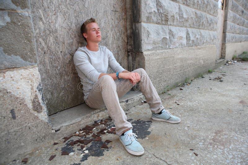 Der Jugendliche, der in einer Gasse mit Augen sitzt, schloss lizenzfreies stockbild