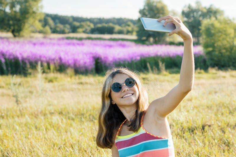 Der Jugendliche des jungen Mädchens, der in Natur geht, wird auf mobilem Smartphone, purpurrotes Lavendelfeld des sonnigen Sommer stockfotos