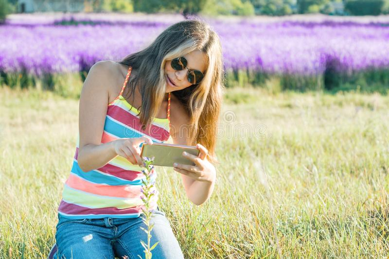 Der Jugendliche des jungen Mädchens, der in Naturphotographien geht, blühen Anlage auf mobilem Smartphone, Sommertagespurpurroter lizenzfreies stockbild