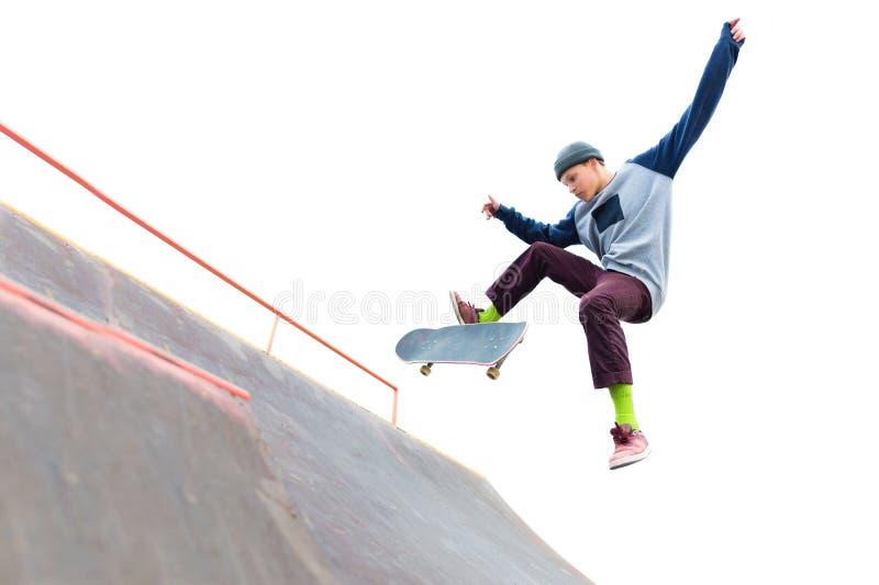 Der Jugendlichskateboardfahrer in der Kappe tut einen Trick mit einem Sprung auf der Rampe im skatepark Schlittschuhläufer und Ra lizenzfreie stockfotografie