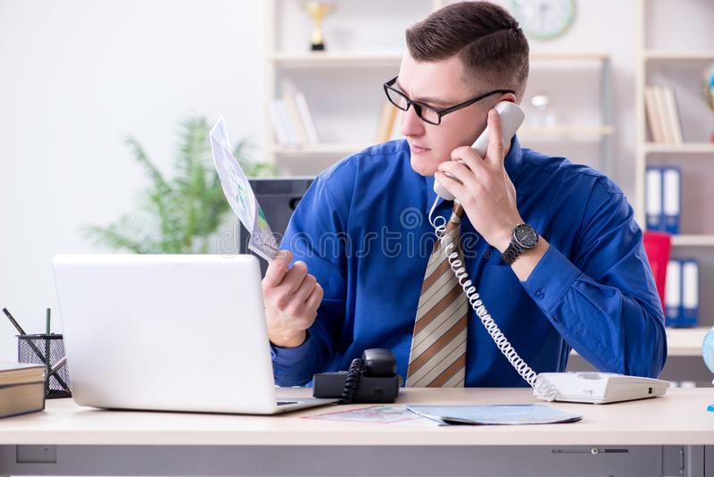 Der junge Angestellte, der für Urlaubsreise sich vorbereitet lizenzfreie stockbilder