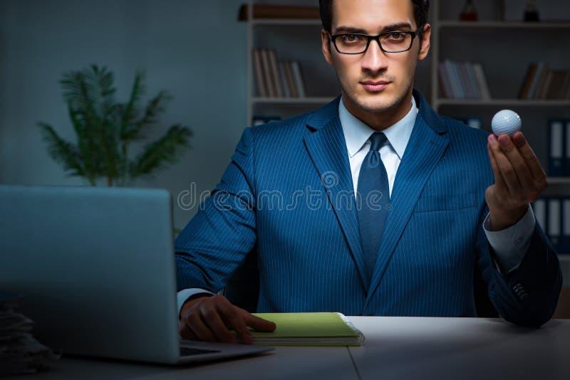 Der junge Angestellte mit Golfball im Büro stockbild