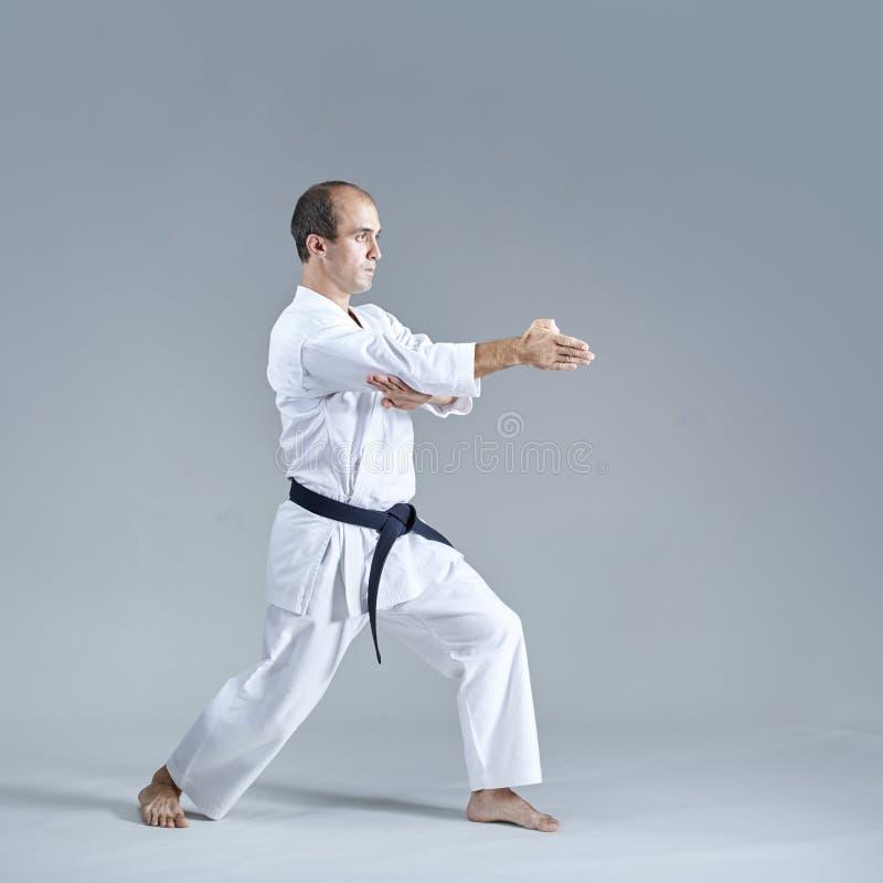 Der junge Athlet, der formales Karate tut, trainiert auf einem grauen Hintergrund lizenzfreie stockfotografie