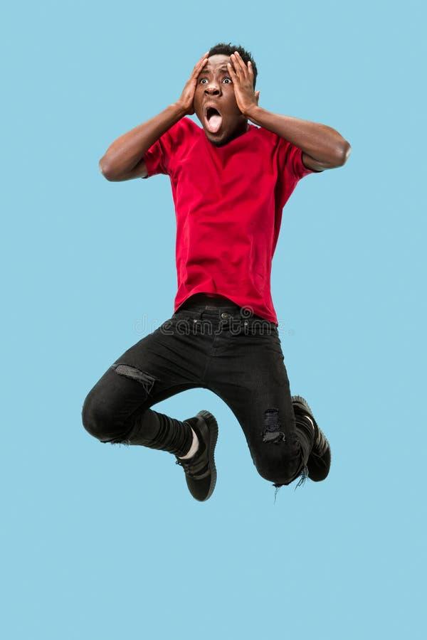Der junge attraktive Mann, der beim Springen überrascht schaut stockbilder