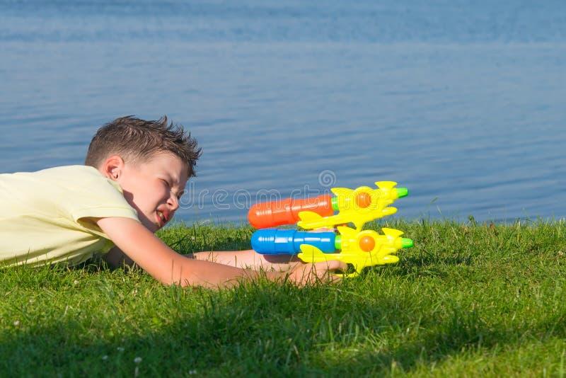 Der Junge, auf dem Hintergrund einer schönen Landschaft, spielend mit einem Wasserwerfer, justiert auf das Ziel, Nahaufnahme lizenzfreie stockbilder