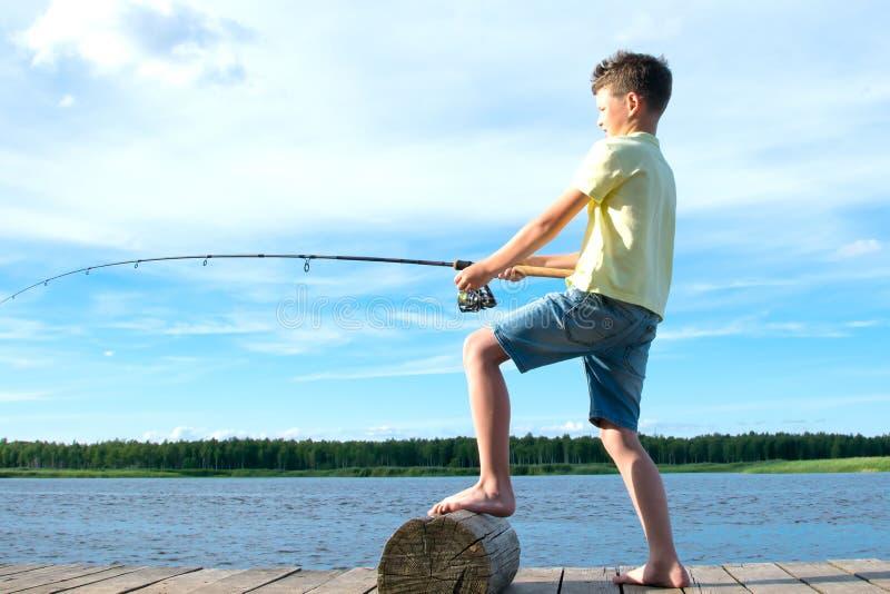 Der Junge auf dem Pier, gegen den blauen See und den Himmel, zieht den Fang auf einer Angelrute stockfotos