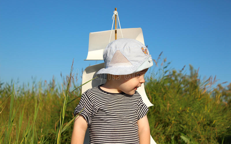 Der Junge auf einem Hintergrund von Papiersegeln und von blauem Himmel lizenzfreie stockbilder