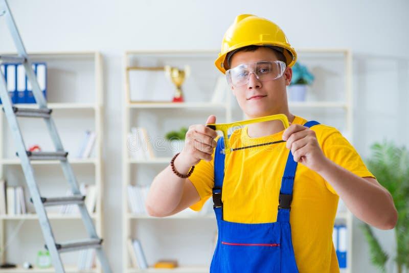 Der junge Auftragnehmer, der Reparatur tut, arbeitet im Büro stockbild