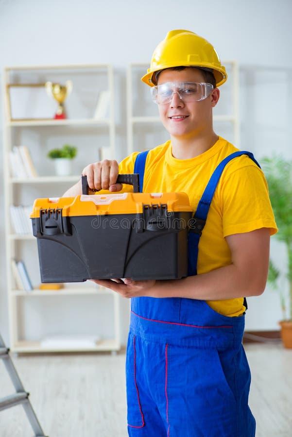 Der junge Auftragnehmer, der Reparatur tut, arbeitet im Büro lizenzfreies stockfoto
