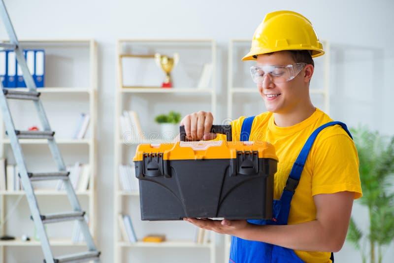 Der junge Auftragnehmer, der Reparatur tut, arbeitet im Büro stockfoto