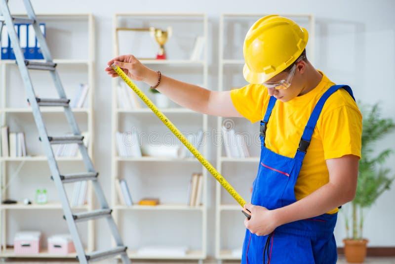 Der junge Auftragnehmer, der Reparatur tut, arbeitet im Büro lizenzfreie stockbilder