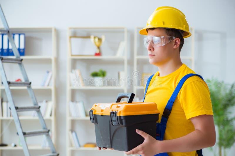 Der junge Auftragnehmer, der Reparatur tut, arbeitet im Büro lizenzfreie stockfotografie