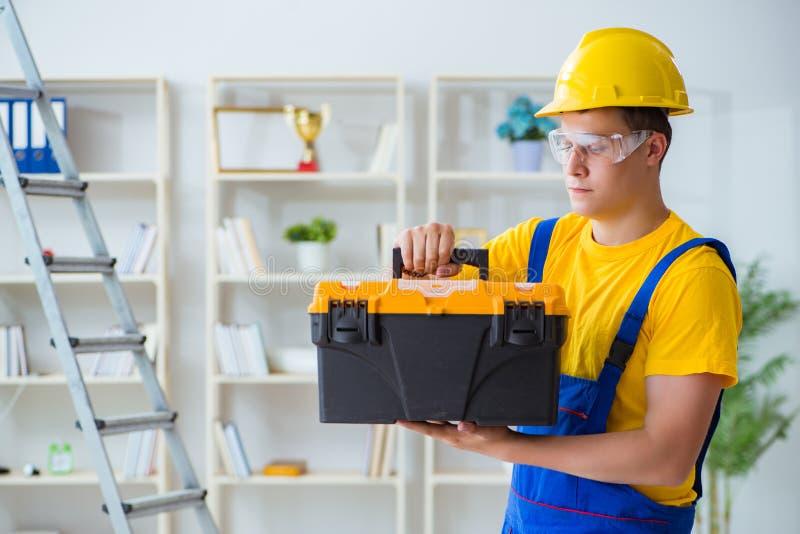 Der junge Auftragnehmer, der Reparatur tut, arbeitet im Büro lizenzfreie stockfotos