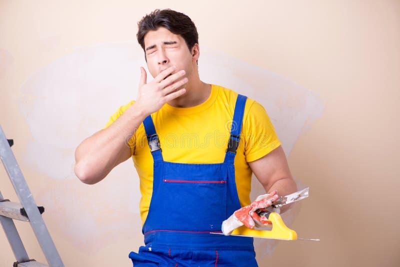 Der junge Auftragnehmerangestellte, der Gips auf Wand aufträgt lizenzfreies stockfoto