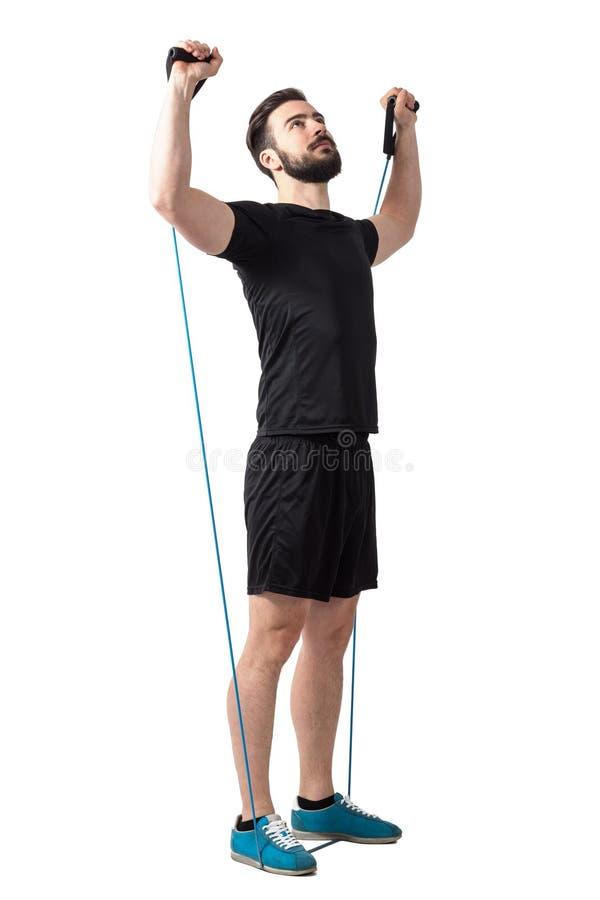 Der junge bärtige Athlet, der Schultern tut, trainieren mit Widerstandgummibändern lizenzfreies stockbild