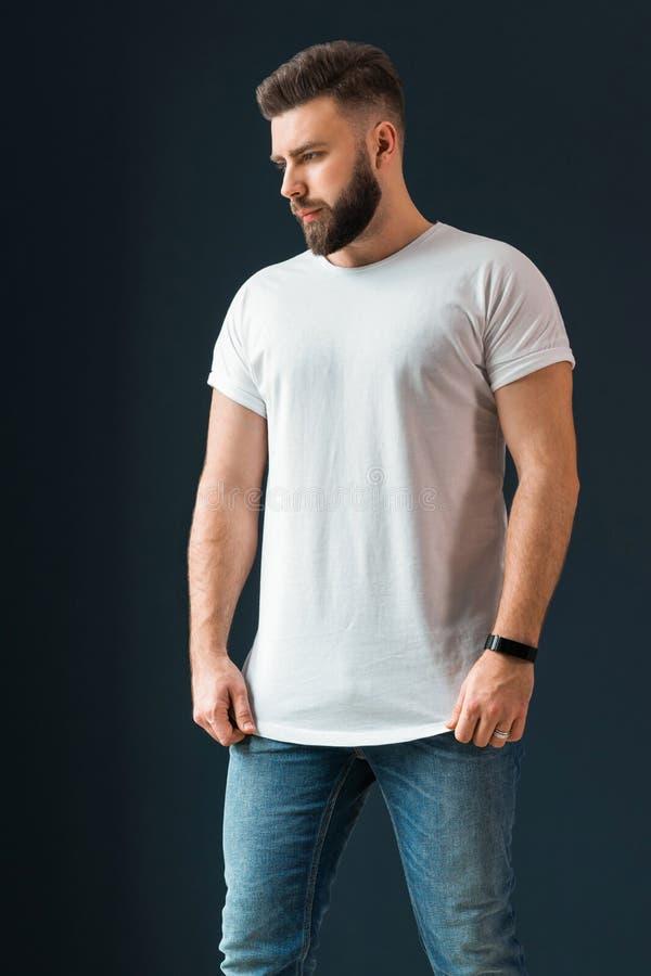 Der junge bärtige hübsche Hippie-Mann, gekleidet im weißen T-Shirt mit kurzen Ärmeln und Jeans, steht zuhause lizenzfreie stockbilder
