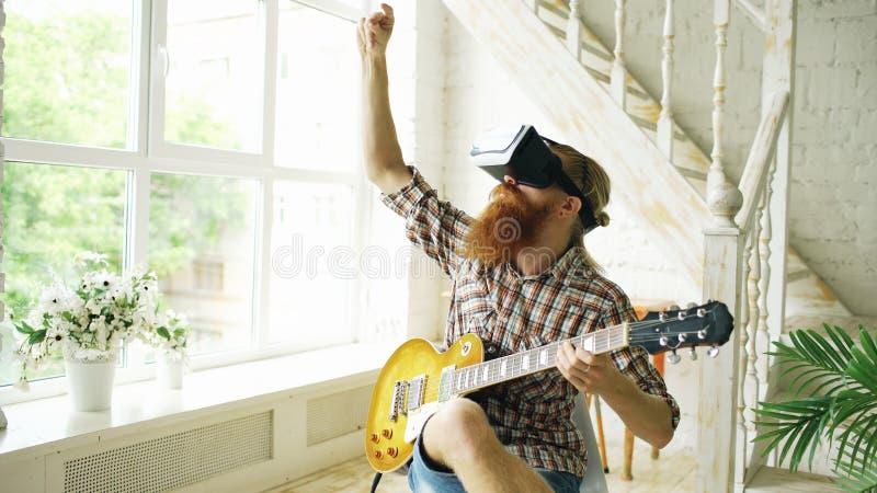 Der junge bärtige Mann, der auf dem Stuhl lernt, Gitarre unter Verwendung Kopfhörers VR 360 zu spielen sitzt und glaubt ihm Gitar stockfotografie