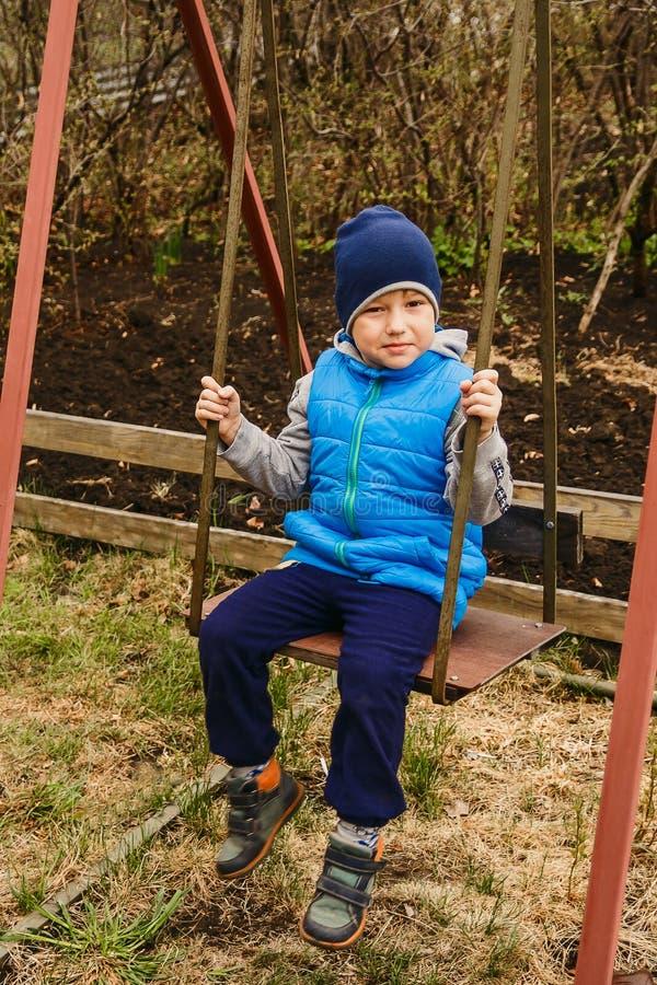 Der Junge in der blauen Weste und der Hut, der auf dem Eisen schwingt, schwingen im Garten lizenzfreie stockbilder