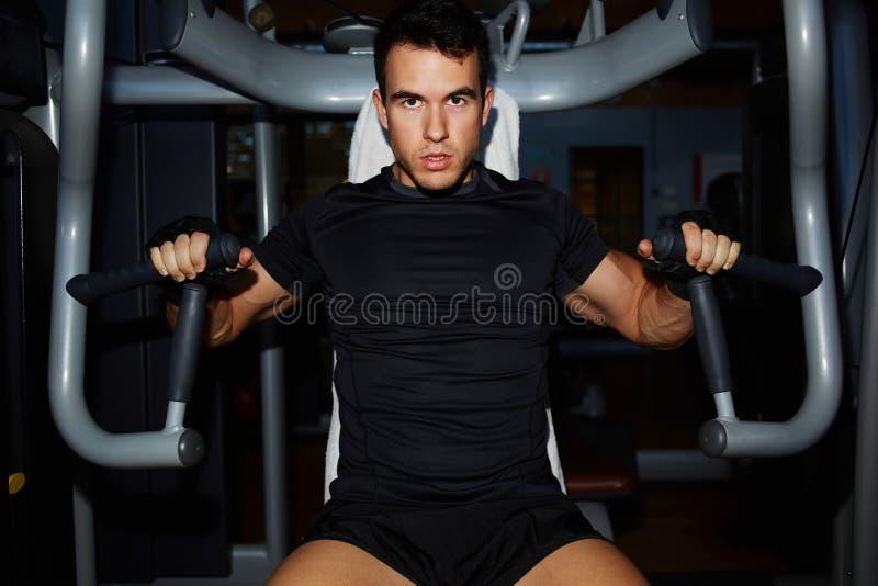 Der junge Bodybuilder, der mit Kasten ausarbeitet, mischt auf Pressemaschine mit lizenzfreie stockfotografie
