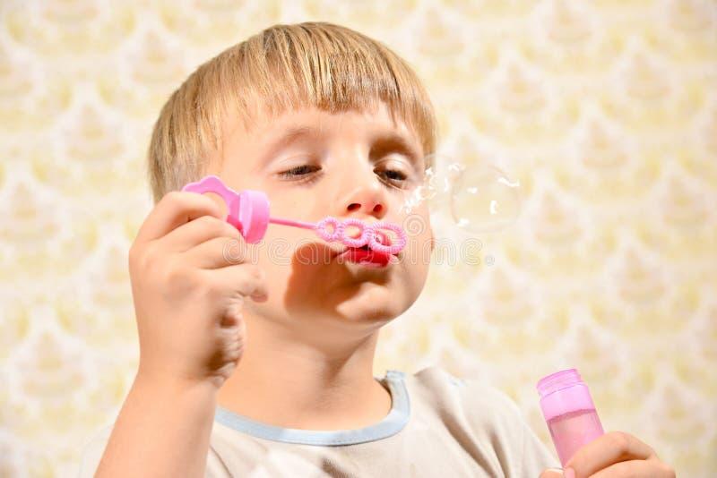 Der Junge brennt Seifenblasen, Nahaufnahme durch lizenzfreie stockfotos