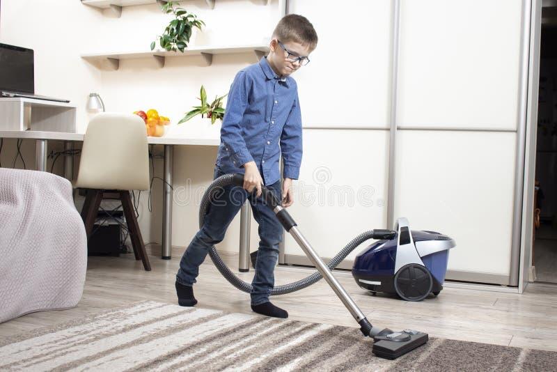 Der Junge in den Gläsern und in einem blauen Hemd säubert die Wohnung Staubsaugen der Wohnung mit einem Staubsauger durch einen s lizenzfreie stockfotos