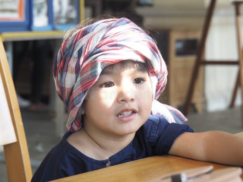 Der Junge, der den Lendenschurz auf seinem Kopf einwickelte, saß und stand still lizenzfreies stockfoto