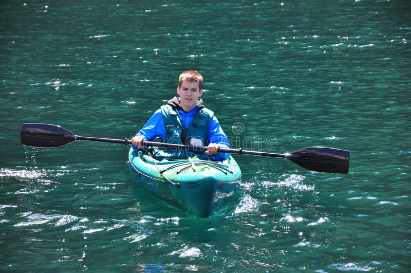 Der Junge, der auf Grün Kayak fährt, tönte Ozean lizenzfreie stockbilder
