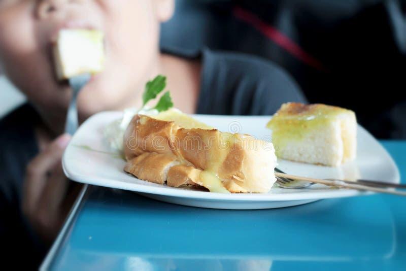Der Junge, der Brot, Butter isst, überstieg mit dem köstlichen Vanillepudding lizenzfreie stockfotos