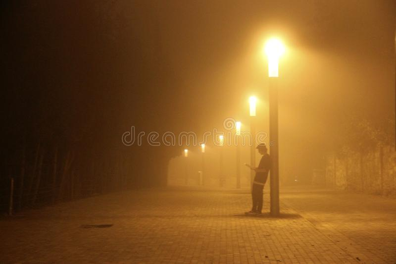 Der Junge, der ein Buch auf der Straße unter einer Lampe liest stockfotografie