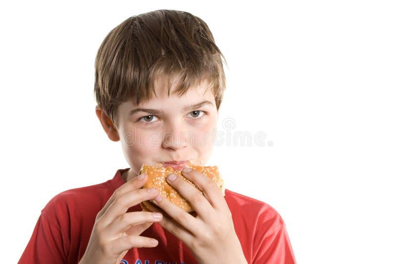 Der Junge, der einen Hamburger isst. stockfoto