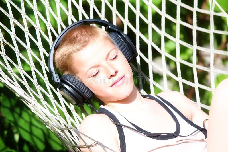 Der Junge, der in einer Hängematte liegt und hören Musik auf Kopfhörern Sommer stockbild