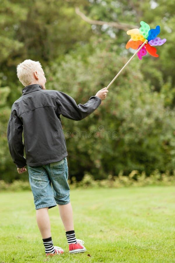 Der Junge, der schwarze Jacke trägt, hält buntes Karussell lizenzfreie stockfotografie