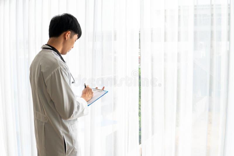 Der junge Doktor machte einen Bericht von den Patientenakten lizenzfreie stockfotos