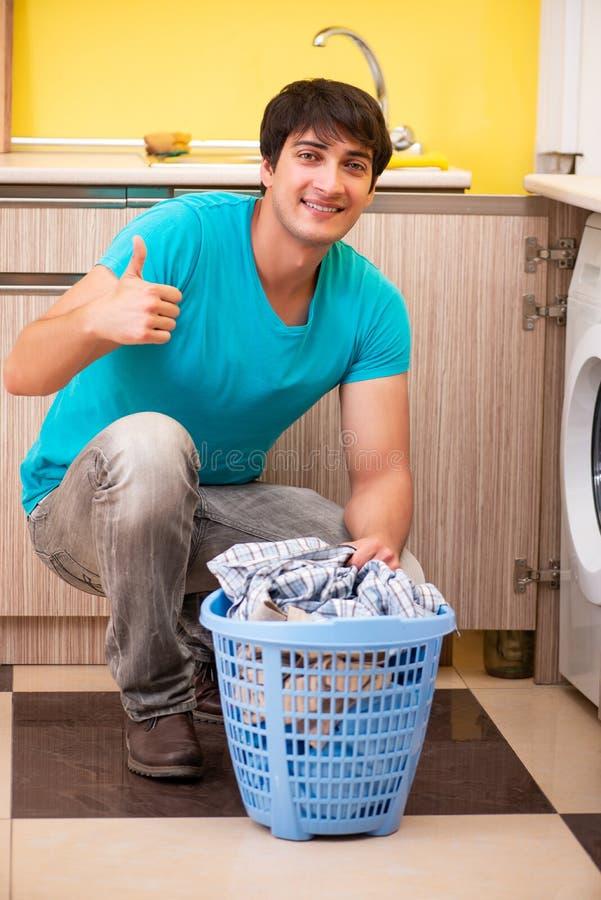 Der junge Ehemannmann, der zu Hause Wäscherei tut stockfotografie